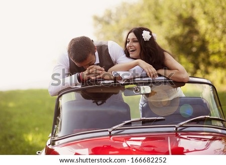 Gorgeous bride and groom having fun with red retro car in nature - stock photo