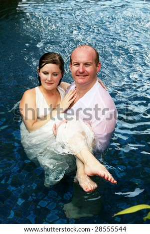 Gorgeous bride and groom in the water during a trash the dress photo shoot.