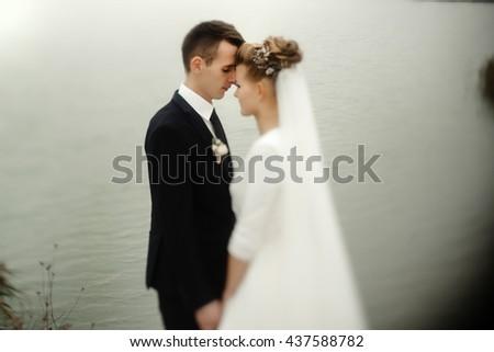 gorgeous bride and stylish groom gently hugging at sandy beach lake, beautiful moment, luxury wedding - stock photo