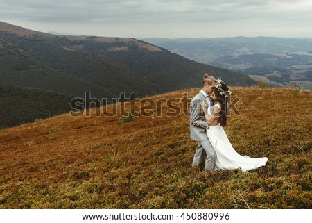 gorgeous bride and stylish groom hugging,  boho wedding couple, luxury ceremony at mountains with amazing view, space for text - stock photo