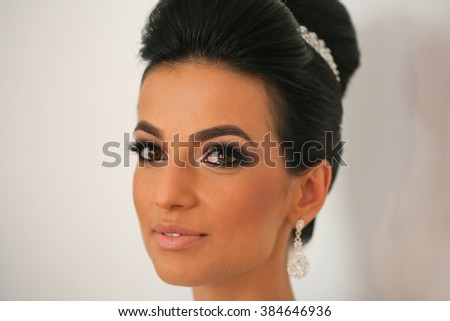 Gorgeous bride getting professional makeup on wedding day - stock photo