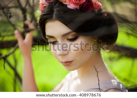 Gorgeous bride with wedding make up and neutral lips staying near the trees with flowers in her head. Floral crown. Fashion  Fashion Brunette Portrait. Wedding.  Beautiful bride waiting for her groom. - stock photo