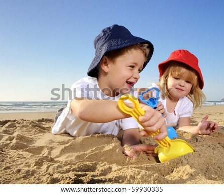 Gorgeous brother and sister ages 4 and 2 have fun digging in the sand at the beach - stock photo