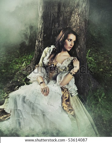 Gorgeous brunette beauty in a old-fashioned dress in a forest - stock photo