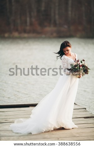 Gorgeous brunette bride in elegant dress holding bouquet  posing near forest and lake - stock photo