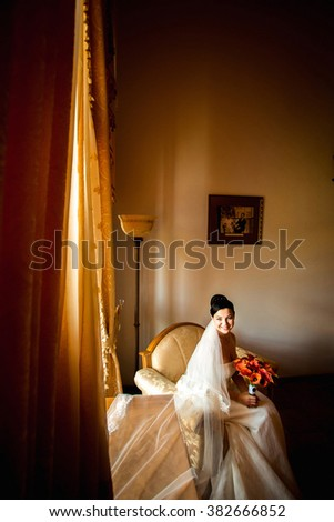 Gorgeous brunette bride in luxury interior at home waiting for groom. Romantic rich brunette bride in luxurious wedding dress in expensive interior with bouquet of red flowers with copy space. - stock photo