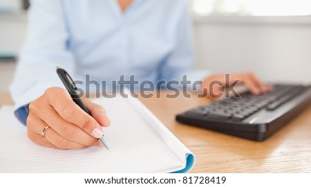 gorgeous brunette businesswoman typing and writing in her office - stock photo