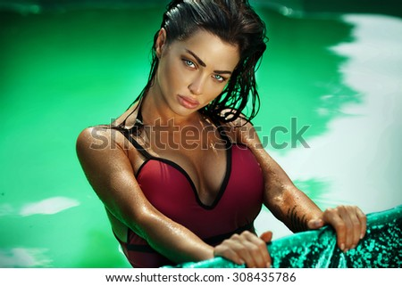 Gorgeous brunette sexy woman posing in swimming pool, wearing fashionable swimsuit, looking at camera. Portrait photo. Summertime. - stock photo