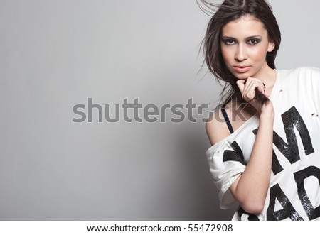 Gorgeous brunette under the flow of wind enigmatic looks and poses - stock photo
