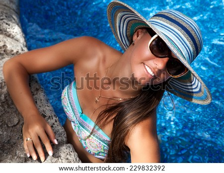 Gorgeous brunette woman in straw hat smiling at you while resting on the side of a brilliant blue pool