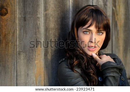 Gorgeous brunette woman leaning against a fence