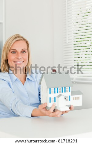 Gorgeous businesswoman showing model house looking into the camera in her office - stock photo