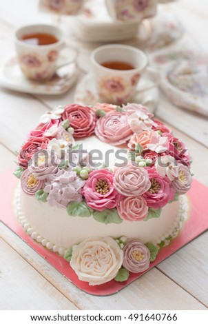Gorgeous cake covered in roses made of butter cream icing on white wooden background
