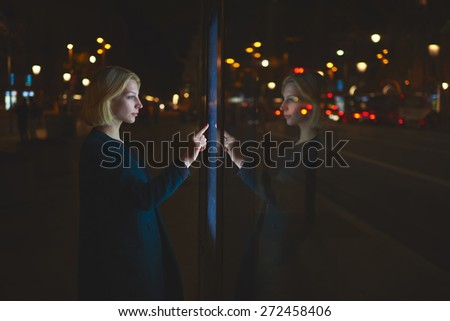 Gorgeous caucasian businesswoman touching sensitive screen of smart city bus stop in night city with out-of-focus lights, female doing internet money payment with automated teller machine,filter image - stock photo