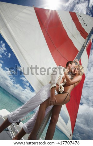 Gorgeous couple kissing, standing on sail boat, catamaran under caribbean sun. Fashion style picture. - stock photo