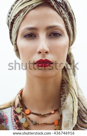 Gorgeous eastern woman standing with nice make-up wearing silk turban, ethnic necklace and luxurious  pareo cover up beachwear. Vintage style. Close up. Outdoor shot