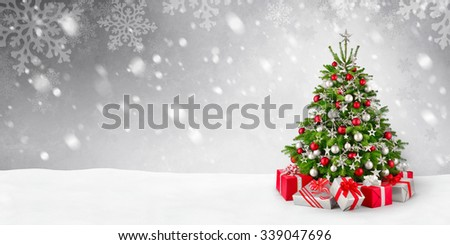 Gorgeous elegant Christmas tree with gifts in red and silver on a panoramic snow background - stock photo