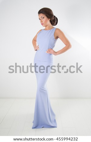 Gorgeous Elegant Woman In Beautiful Bright Blue Gown With Perfect Classic Hairstyle And Makeup Posing With Hands On Hips And Looking At The Camera, Full-Length Studio Shot Over White Background - stock photo