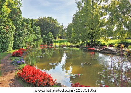 Gorgeous European park. Quiet picturesque pond surrounded by a bright colored shrubs and trees