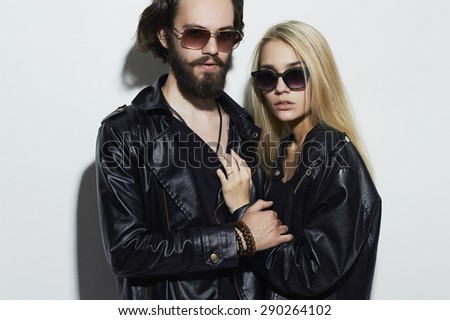 gorgeous fashion beautiful couple in black clothes wearing trendy glasses and posing over white background together. Hipster boy and girl. Bearded young man and blonde in sunglasses - stock photo