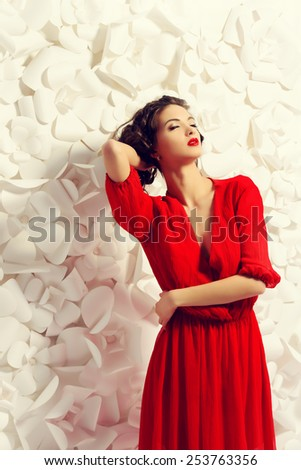 Gorgeous fashion model in bright red dress over background of white paper flowers. Beauty, fashion. Love concept.  - stock photo