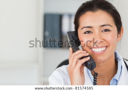 Gorgeous female doctor on the phone and posing in her office - stock photo