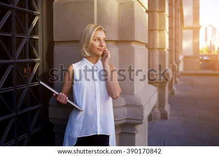 Gorgeous female lecturer of university calls via cell telephone and holds laptop computer while stands in the fresh air, young woman office worker is having mobile phone conversation during work break - stock photo