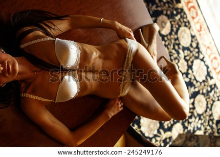 Gorgeous female shows her sexy body and thin waist in seductive position - stock photo