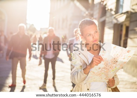 Gorgeous female tourist with a map discovering a foreign city (shallow DOF; color toned image) - stock photo