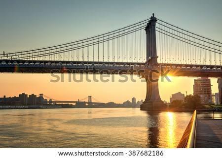 Gorgeous fiery orange sunset with a sunburst behind Brooklyn Bridge, New York, viewed across the water of the East River from a pier - stock photo