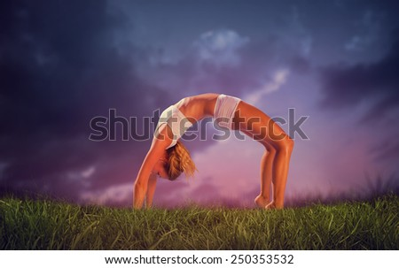 Gorgeous fit blonde in crab pose against blue sky over grass - stock photo