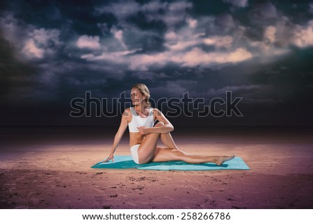 Gorgeous fit blonde in seated yoga pose against dark cloudy sky - stock photo