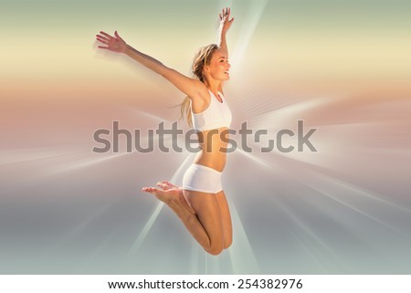 Gorgeous fit blonde jumping with arms out against abstract background - stock photo