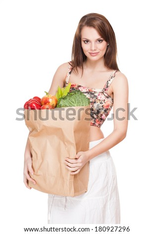 Gorgeous fit slender young brunette woman with bag of fresh vegetables.