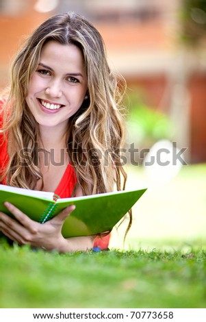 Gorgeous girl studying outdoors lying on the floor - stock photo