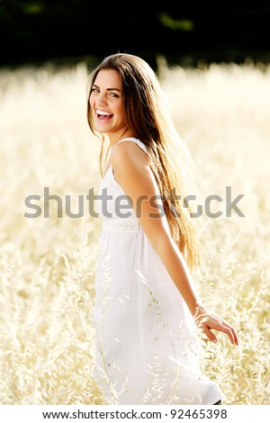 gorgeous girl walking in the field of long grass and dragging her hand touching the dry grass while laughing and smiling, carefree healthy lifestyle - stock photo