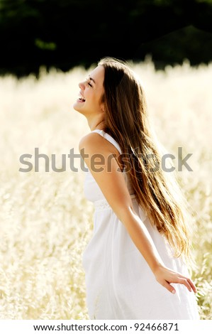 gorgeous girl walking in the field of long grass and dragginhg her hand touching the dry grass while laughing and smiling, carefree healthy lifestyle - stock photo