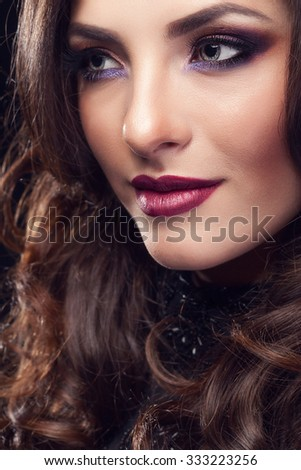 Gorgeous girl with perfect make up looking away of the camera. Studio shooting. Beauty and fashion make up portrait
