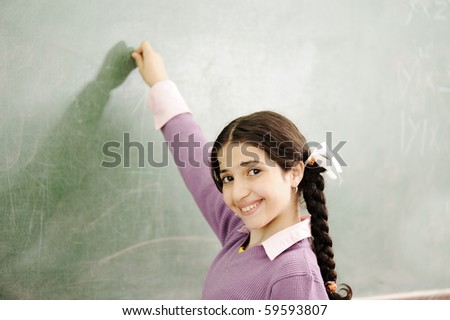 Gorgeous girl writing on classroom board - stock photo