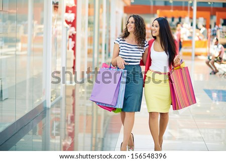 Gorgeous girlfriends with paperbags walking down trade center and looking at shopwindows - stock photo