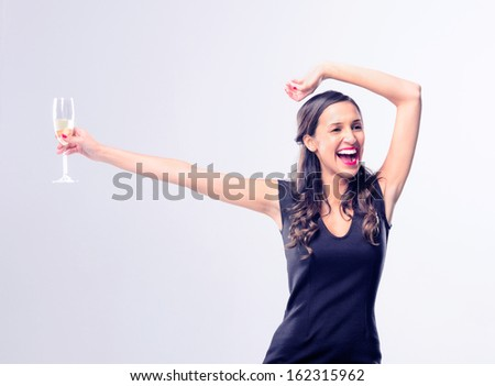 Gorgeous glamourous woman dancing and enjoying herself while holding a glass of champagne, wearing a little black dress for new years eve party celebration  - stock photo