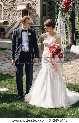 gorgeous happy brunnete bride and elegant stylish groom having wedding ceremony on the background of arch