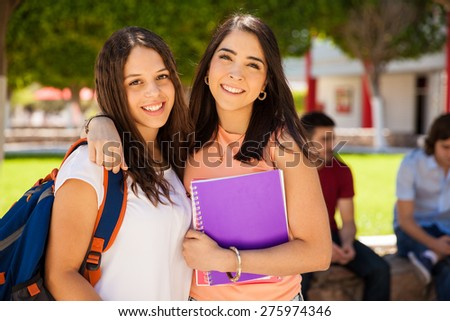 Gorgeous Hispanic college girls hugging each other and hanging out at school