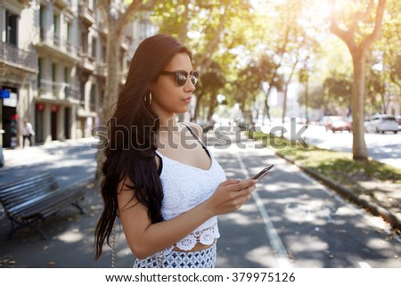 Gorgeous Hispanic woman chatting on mobile phone while standing in the street in summer day, pretty female with long brunette hair reading news on cell telephone while waiting for boyfriend outdoors - stock photo