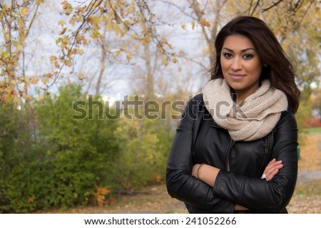 Gorgeous Hispanic woman posing with arms cross outside during autumn - stock photo