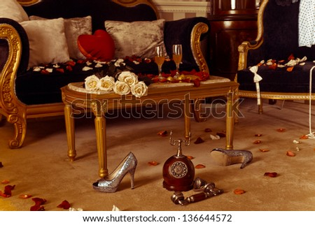 Gorgeous hotel room prepared for celebration with two glasses of wine roses and flower petals - stock photo