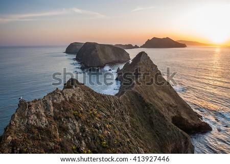 Gorgeous island coastline, cliffs and sunset. - stock photo