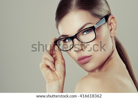 Gorgeous lady in fashionable spectacles looking at camera posing in studio.  - stock photo