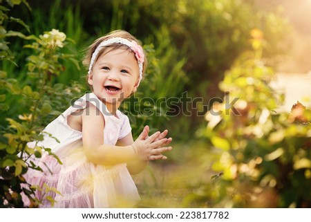 Gorgeous little girl outdoors in green garden having lots of fun - stock photo