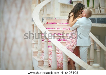 Gorgeous, lovely bride and handsome groom hugging in emotional embrace on stairs. - stock photo